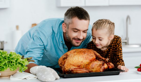 happy father and daughter sniffing freshly baked thanksgiving turkey