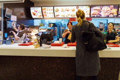 Munich, Germany - October 24, 2017: The girl receives an order in the interior of the McDonald's fast-food restaurant